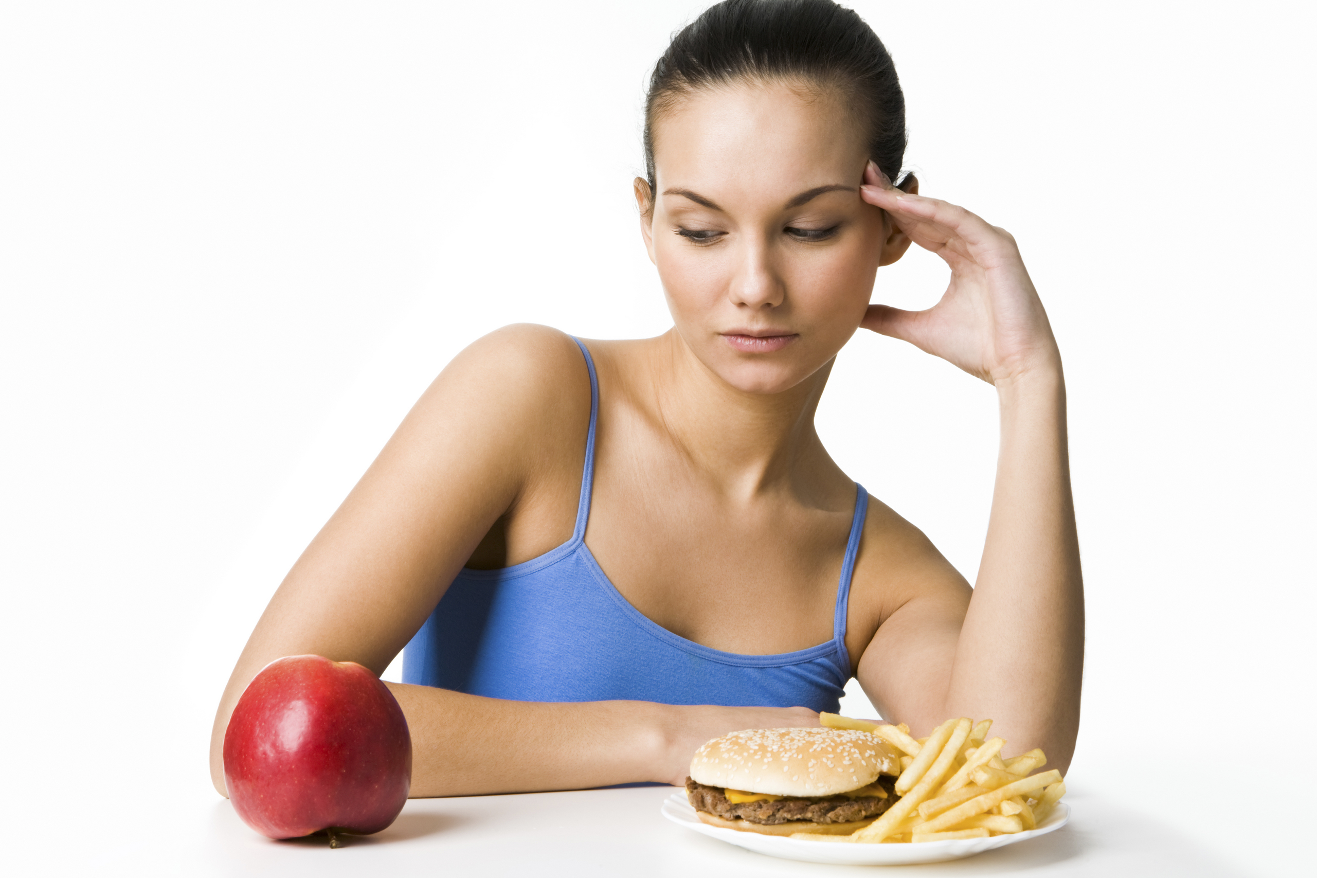 Portrait of pretty young girl deciding what to eat: an apple or hamburger with fried potatoes